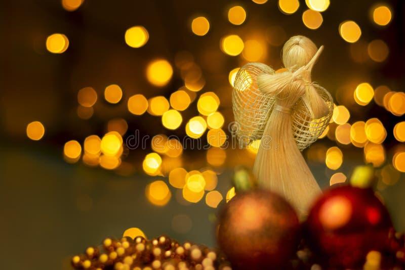 Traditionell handgefertigte Strohpuppe mit Weihnachtsschmuck auf einem verschwommenen Hintergrund mit Lichtern Dramatische Weihna stockfotografie