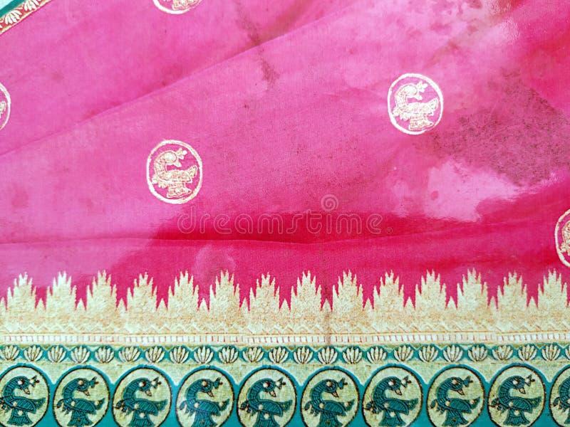 Traditionell handgjord vit, r?d/rosa bl? indisk siden- sari /saree med guld- detaljer, kvinnabruk att b?ra p? den Onam festivalen royaltyfri bild