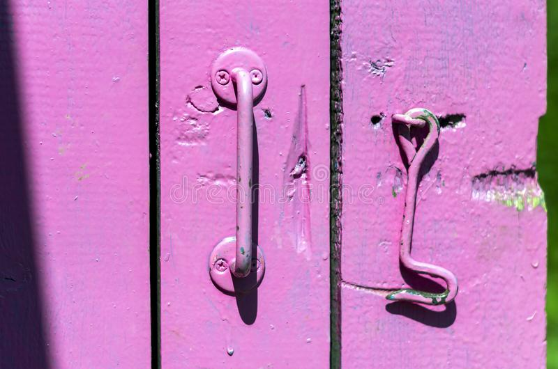 Traditionell handtag och krok p? den gamla tr?d?rren som m?las all i rosa f?rger, p? en ljus solig dag royaltyfri bild