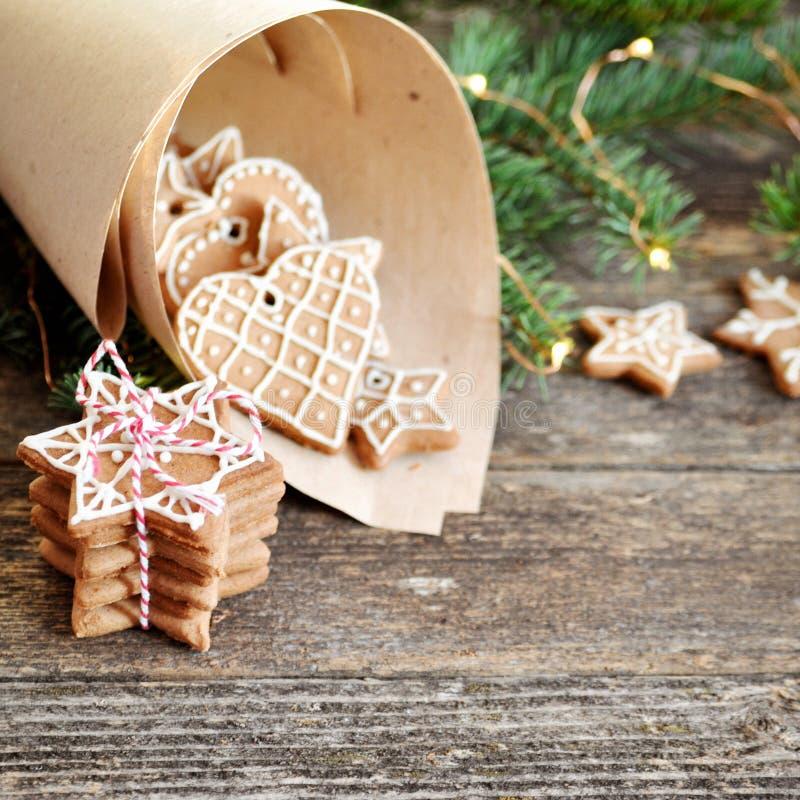 Traditionell hemlagad glasyr på kaka för julpepparkakasocker i papperskuvert på träbakgrund Julgran som dekoreras med royaltyfria bilder