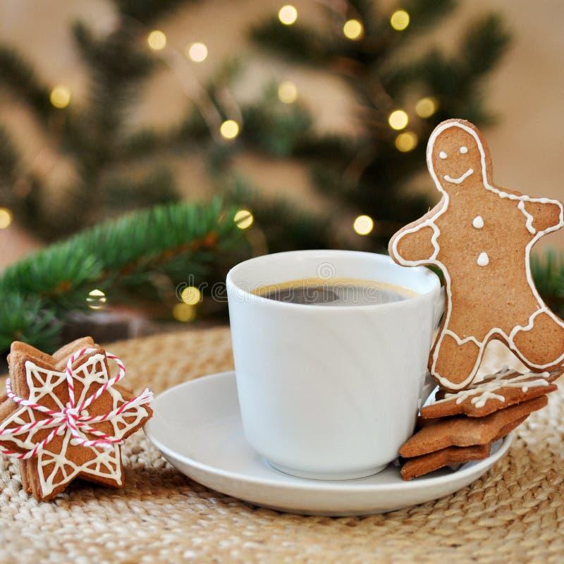 Traditionell hemlagad glasyr på kaka för julpepparkakasocker som formas som en rolig liten man och en kopp av varm espresso på en royaltyfria foton