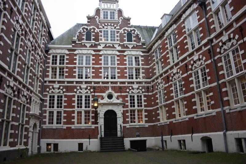 Traditionell inre borggård som omges av högväxta och gamla väggar för röd tegelsten gammal byggnad, holländsk stil för tappning f royaltyfria foton