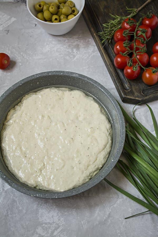Traditionell italienare Focaccia med tomater, oliv och rosmarin Focaccia matlagningprocess, ingredienser Focaccia deg arkivbild