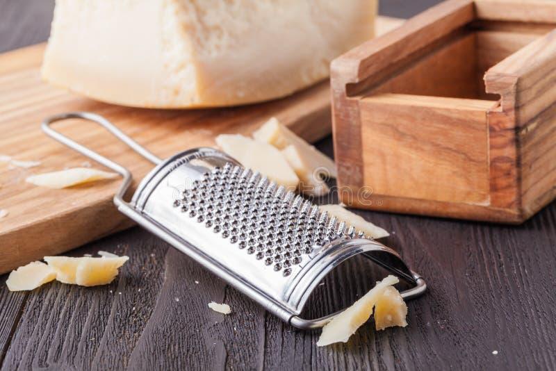 Traditionell italiensk hårdostparmesan och Grana Padano med rivjärnet arkivfoton