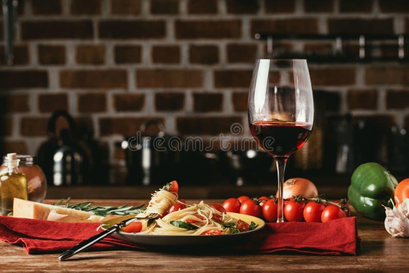 traditionell italiensk pasta med tomater och arugula i platta och exponeringsglas av royaltyfri foto