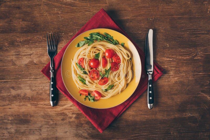 traditionell italiensk pasta med tomater och arugula i platta med kniven och gaffeln arkivfoto