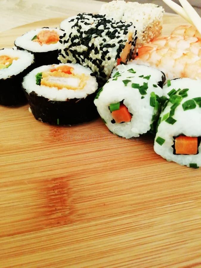 Traditionell japansk mat g?r med den r? fisken Maki och rullar med tonfisk, laxen, räka, krabban och avokadot Regnbågesushirulle, royaltyfria bilder