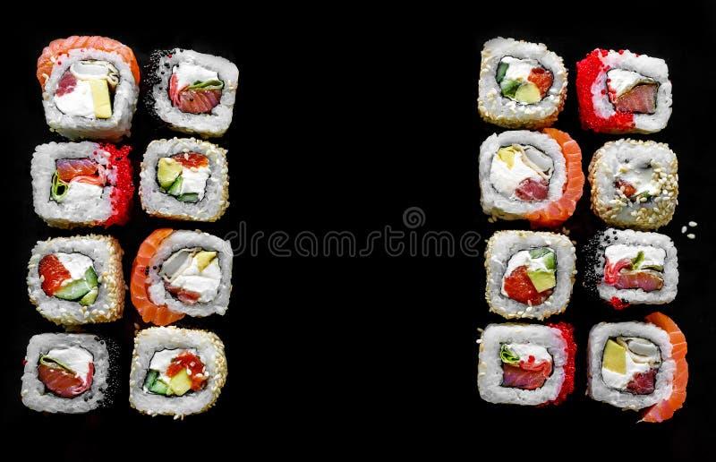 Traditionell japansk mat - sush rullar på svart bakgrund royaltyfri fotografi