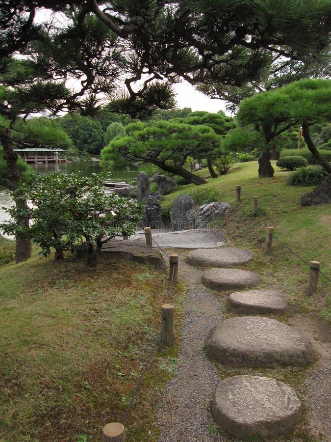 Traditionell japansk promenadträdgård med att kliva stenbana royaltyfri bild