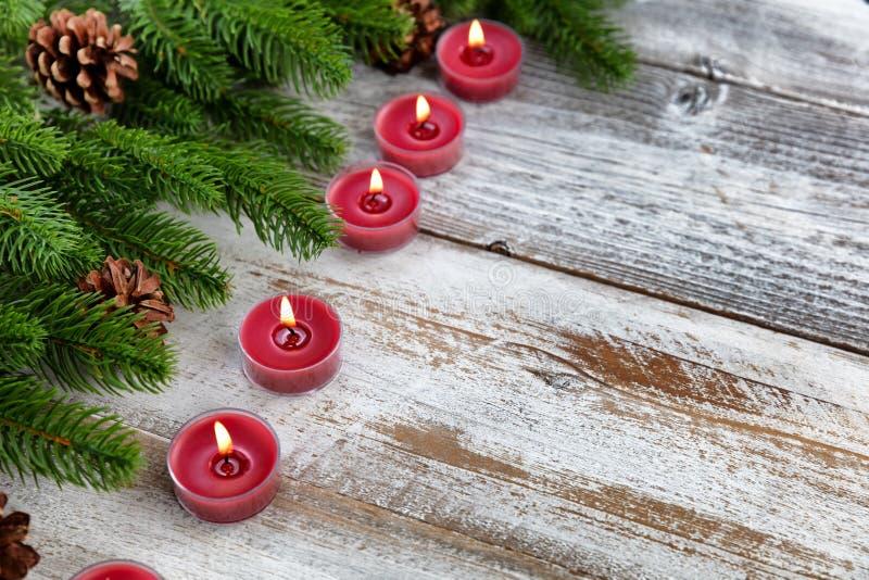 Traditionell jul semestrar stearinljus och vintergröna filialer på vit lantlig träbakgrund arkivbilder