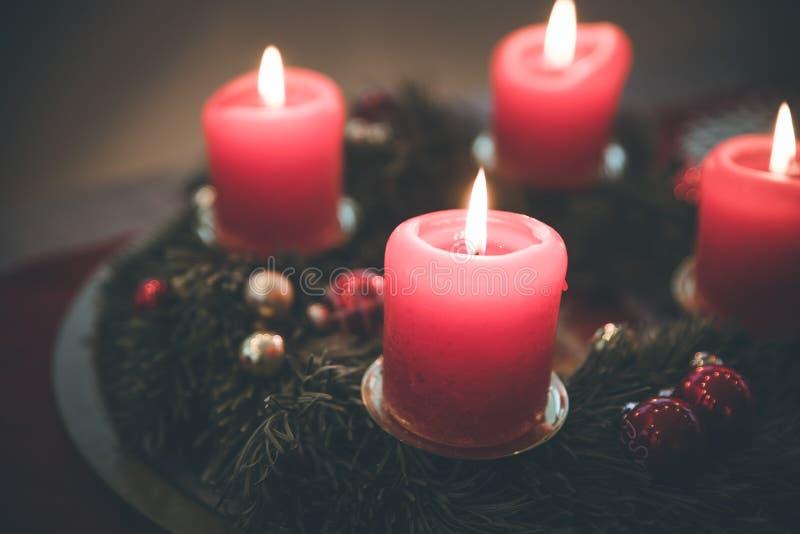 Traditionell julgarnering: Adventkrans med röda ljus arkivbilder