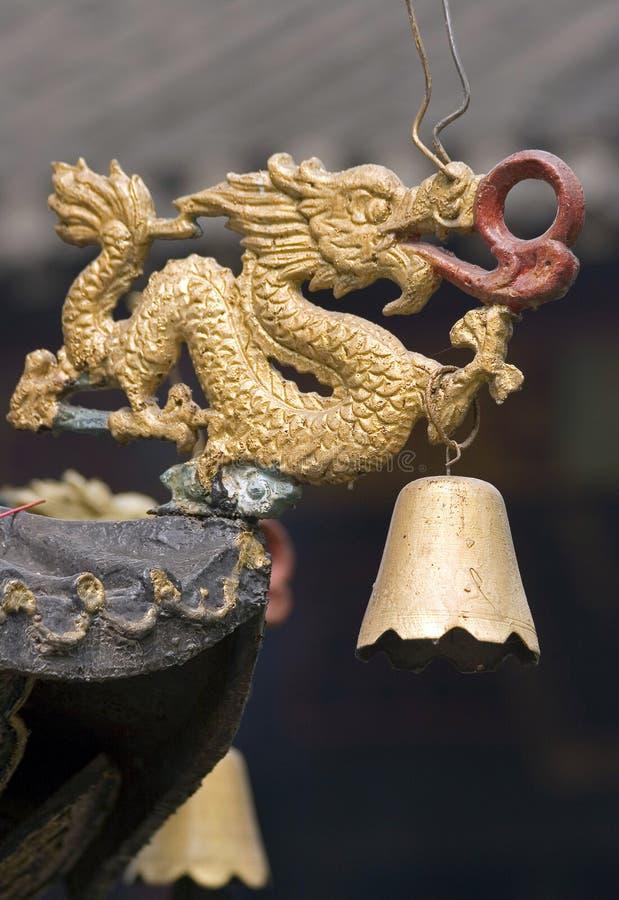 Traditionell kinesisk drake med en klocka på taket av templet arkivfoto