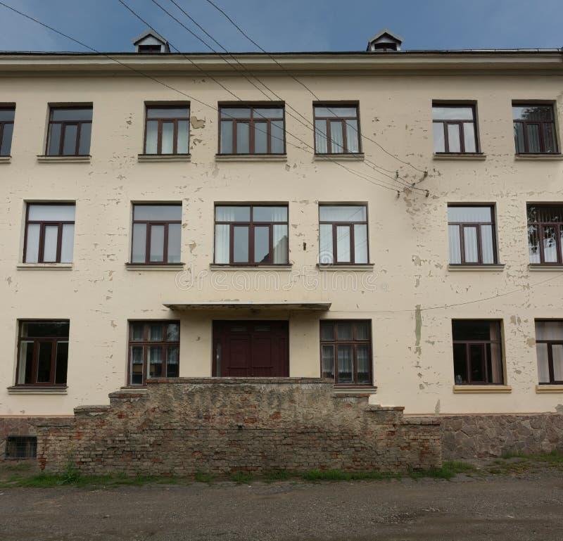 Traditionell klassisk europeisk sovjetisk fasad för skolabyggnad med fönster royaltyfria bilder