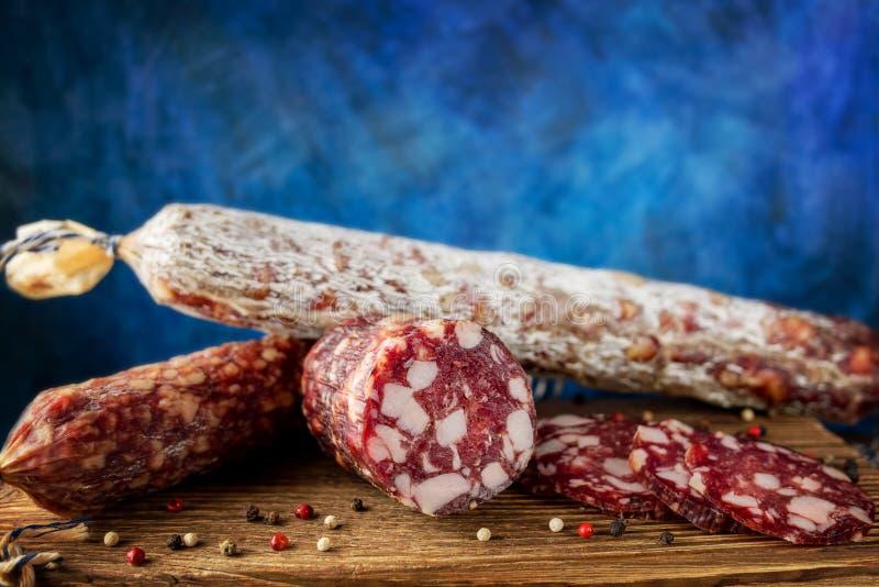 Traditionell korv och korv med formen Skivad korvsalami på träbräde med kryddor N?rbild royaltyfria foton