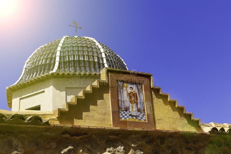 Traditionell kupol med blåa keramiska tegelplattor och bilden av helgonet i den kyrkliga Relleuen, Alicante landskap royaltyfria foton