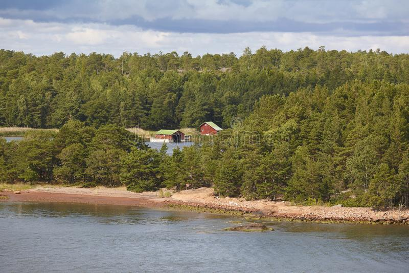 Traditionell lantgård i den finlandssvenska skogen som omges av sjön alar royaltyfri foto