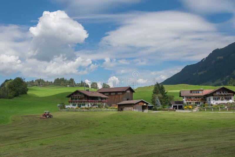 Traditionell lantgårdbyggnad i de tyska fjällängarna som omges av berg, gröna kullar, blå himmel och moln royaltyfri fotografi