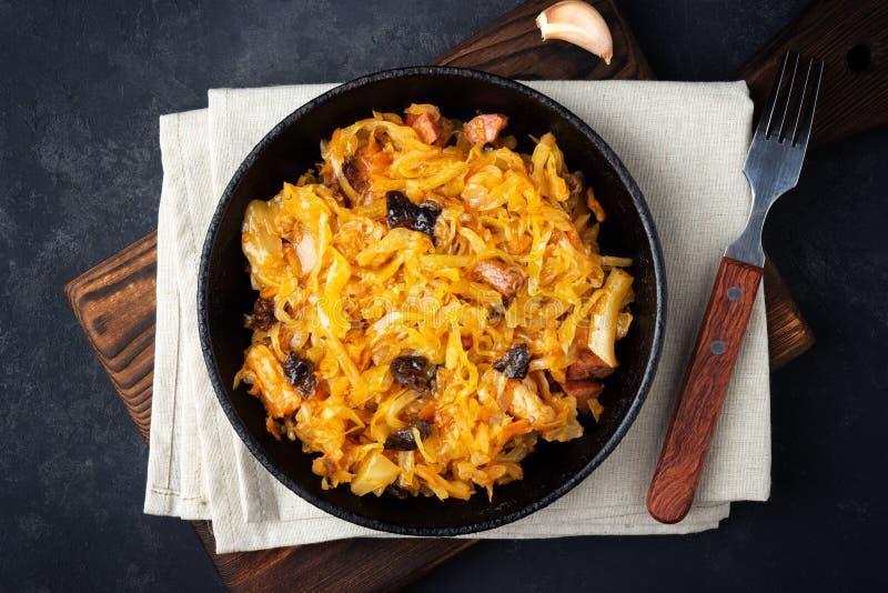 Traditionell maträtt av polermedelkokkonst - Bigos från nya kål, kött och katrinplommoner royaltyfri fotografi