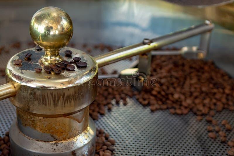 Traditionell metod av att grilla torkade organiska arabicakaffebönor i arbetslista med det öppna rastret för att kyla, bio kaffel royaltyfri bild