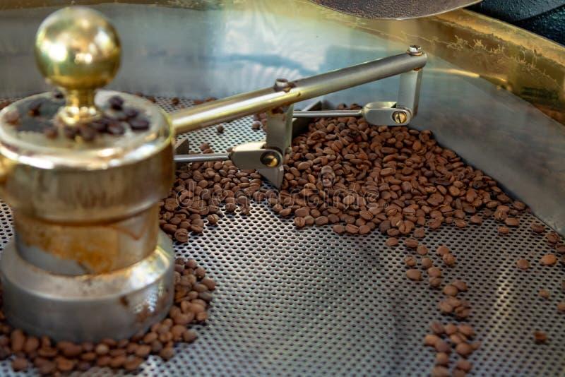 Traditionell metod av att grilla torkade organiska arabicakaffebönor i arbetslista med det öppna rastret för att kyla, bio kaffel fotografering för bildbyråer
