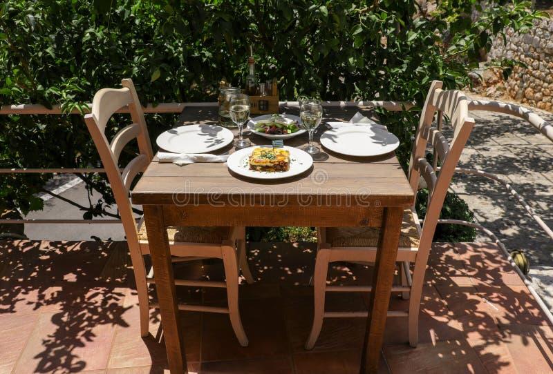 Traditionell moussaka, grekisk sallad för by och vitt vin på trätabellen i grekisk krog arkivbilder