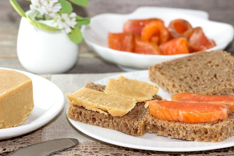 Traditionell norsk frukost, smörgåsar med brun ostbrunost, smörgåsar med gurkan och forell royaltyfri foto