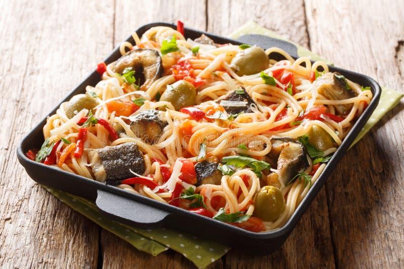 Traditionell pastamaträtt med den grillade ål-, oliv-, peppar- och tomatsåscloseupen på en platta horisontal royaltyfri fotografi