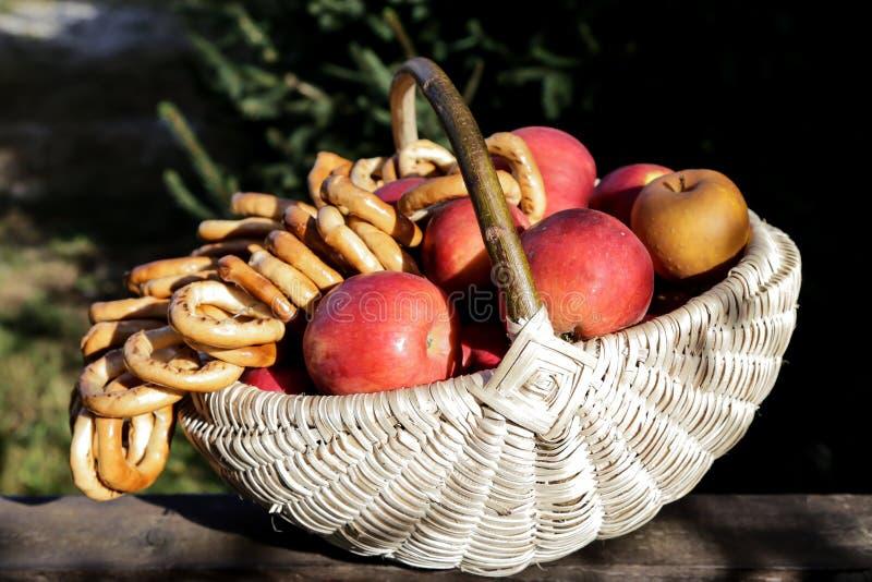 Traditionell rät maskakorg mycket av äpplen och kringlor royaltyfri bild