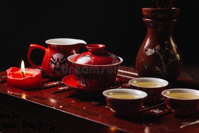 Traditionell röd kinesisk teservis, rött porslin med kinesiska teatermaskeringar för traditioanl arkivfoto