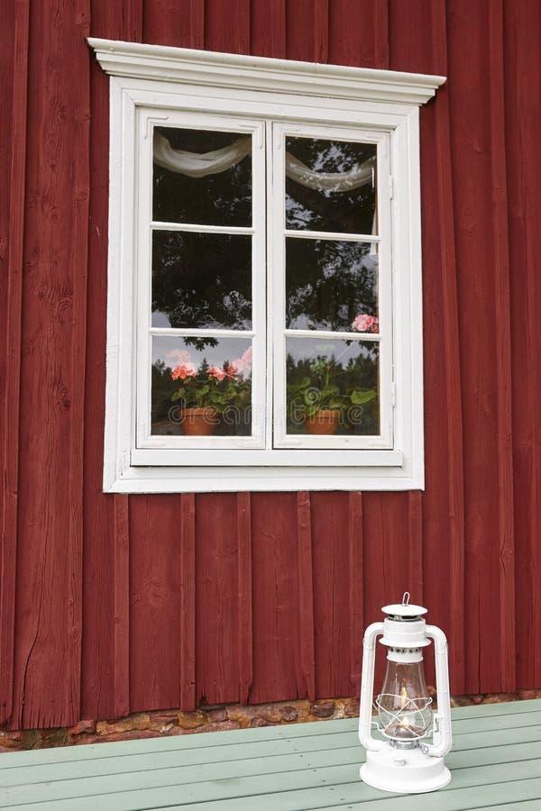 Traditionell röd trälantgårdfasad med fönstret och blommor Finl arkivfoton