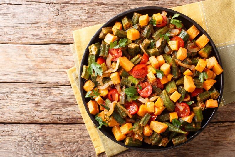 Traditionell receptragu från okra, sötpotatis, tomater, oni royaltyfria foton