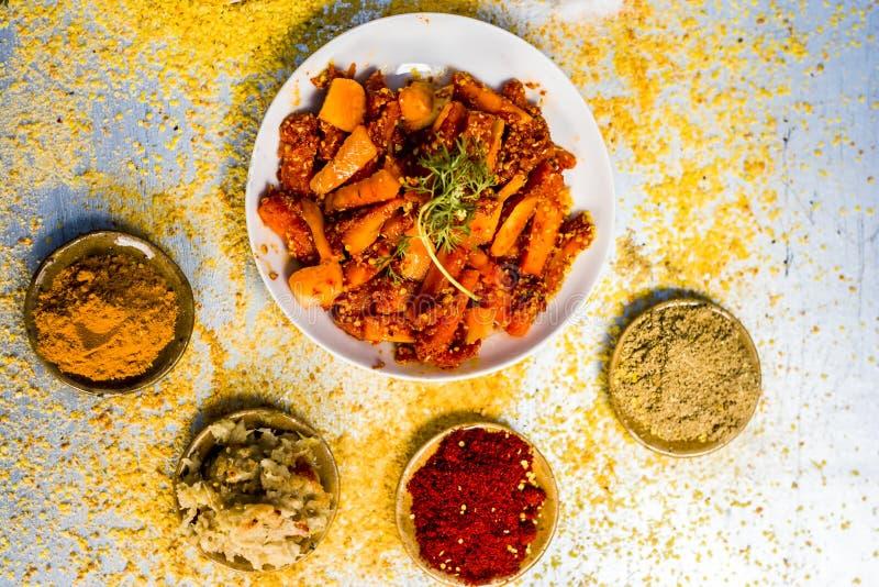 Traditionell/regional morotknipa, Daucuscarotasubsp sativus knipa med ingredienser som pulver f?r r?d peppar och gurkmejapulver arkivfoton