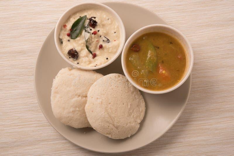 Traditionell södra indisk mat, idli eller overksamt med sambaren och vitkokosnötkokosnöten i den vita plattan arkivfoton