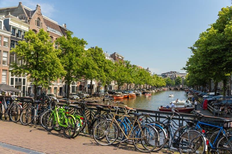 Traditionell sikt av Amsterdam: cyklar och vatten fotografering för bildbyråer