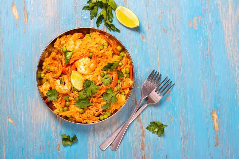 Traditionell spansk paellamaträtt med skaldjur, ärtor, ris och höna royaltyfri fotografi