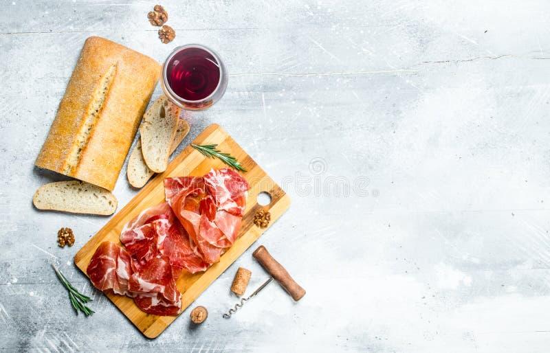 Traditionell spansk skinka med ciabatta och rött vin arkivbilder