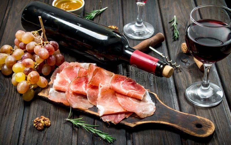 Traditionell spansk skinka med druvor och rött vin fotografering för bildbyråer