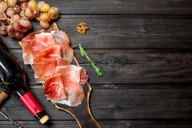 Traditionell spansk skinka med druvor och rött vin royaltyfri fotografi