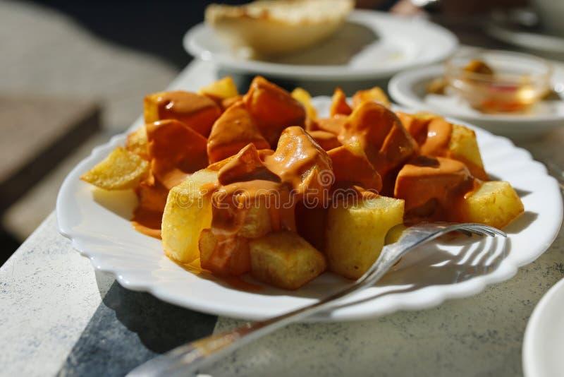 Traditionell spansk tapa bakade potatisar med kryddig sås royaltyfria bilder