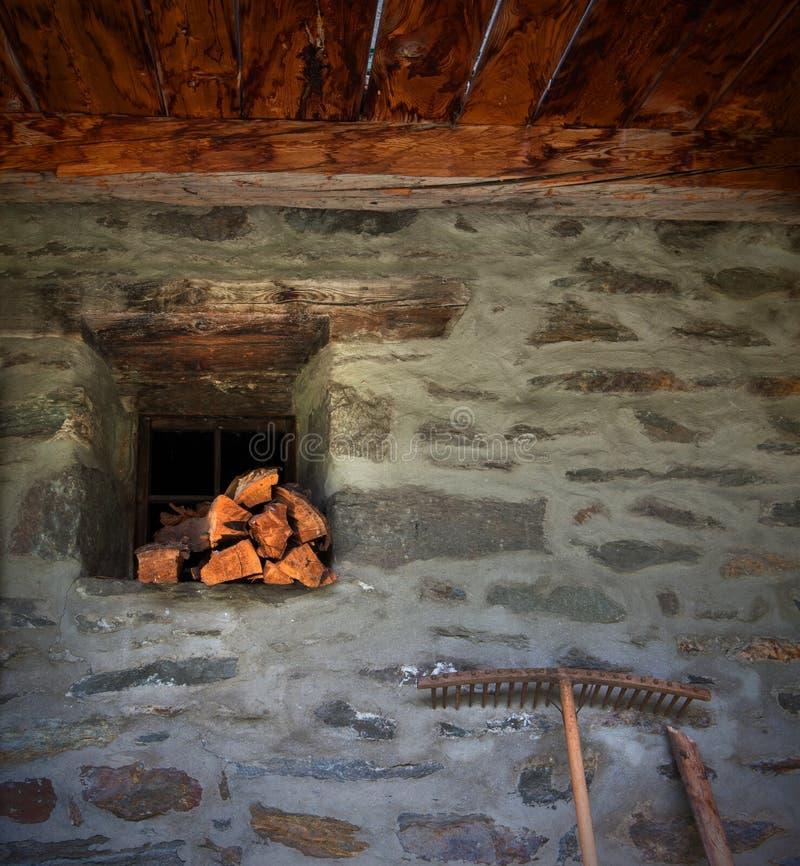 Traditionell stenvägg med staplat vedträ framme arkivbild