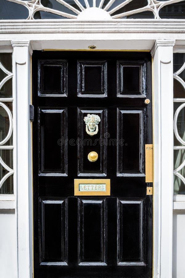 Traditionell svart ingångsdörr med den dekorativa bokstavsasken i Dublin Ireland royaltyfria bilder