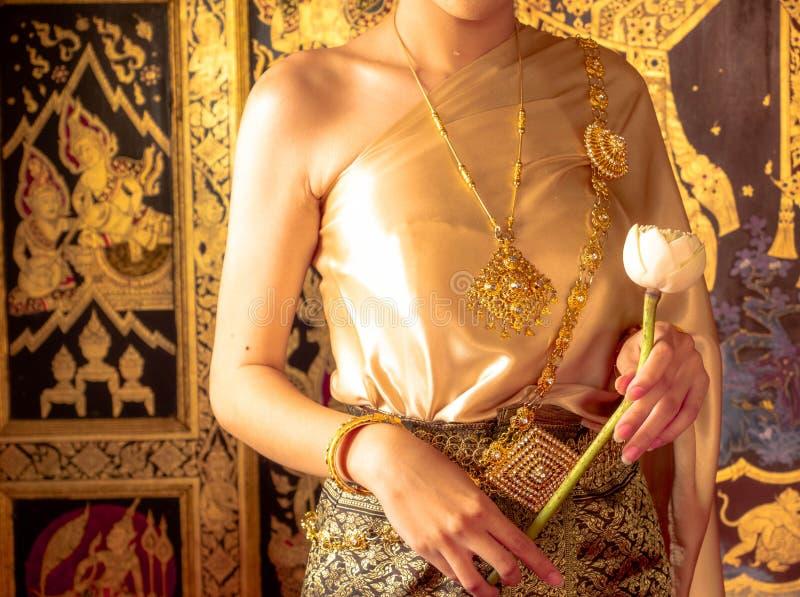 Traditionell thai dräkt med identitet, thailändsk flicka för kvinnor som rymmer en lotusblomma, identitetskultur av Thailand royaltyfria foton