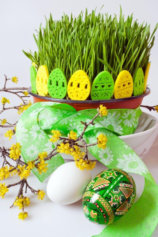Traditionell tjeckisk easter garnering - gröna veteplantor i blomkrukan och de dekorerade äggen med skogskornellris på viten b arkivfoton