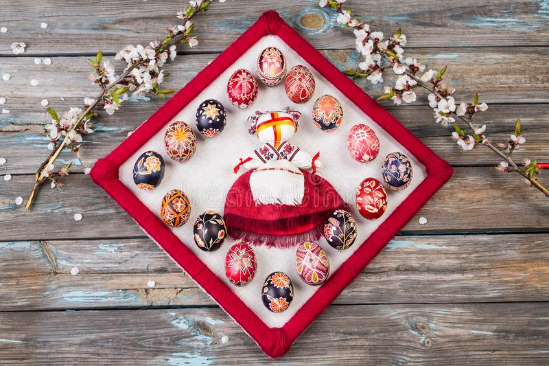 Traditionell ukrainsk dockamotanka eller iklädd medborgarekläder för ragdoll Ragdoll och pysankas Påskägg och körsbär arkivfoto
