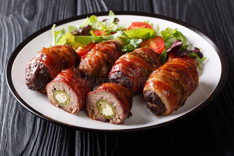Traditionella amerikanska bältdjurägg som stoppas med jalapenoen och ost som slås in i bacon som tjänas som med salladnärbild på  arkivbild