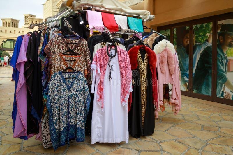 Traditionella arabiska kvinnor och mäns kläder på räknaren av ett litet shoppar arkivbild