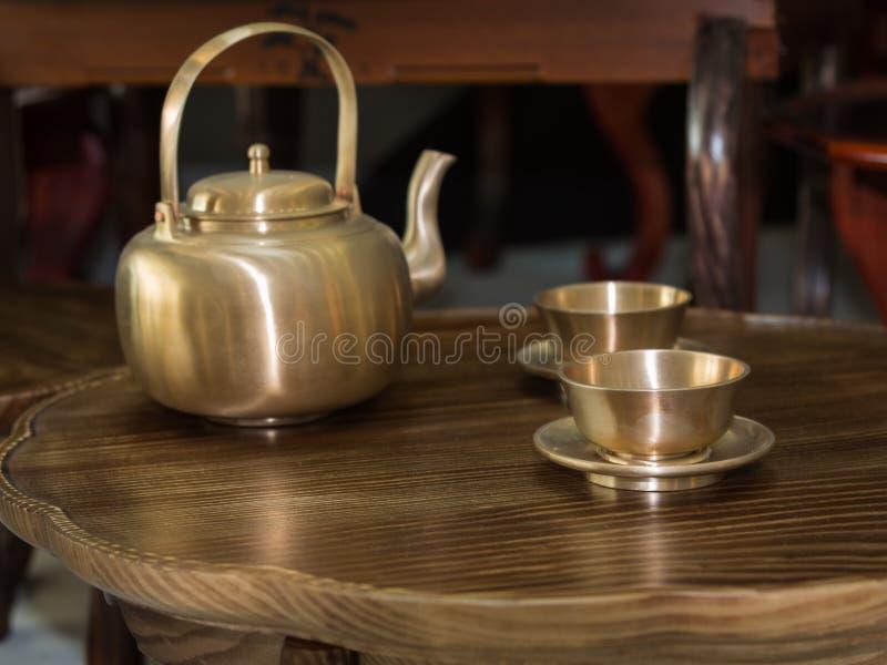 Traditionella asiatiska guld- tekanna och koppar på den lilla trätabellen royaltyfri fotografi