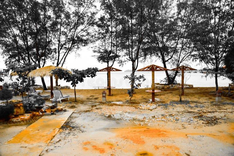 Traditionella avkopplingkojor på den gula sandiga stranden arkivbild