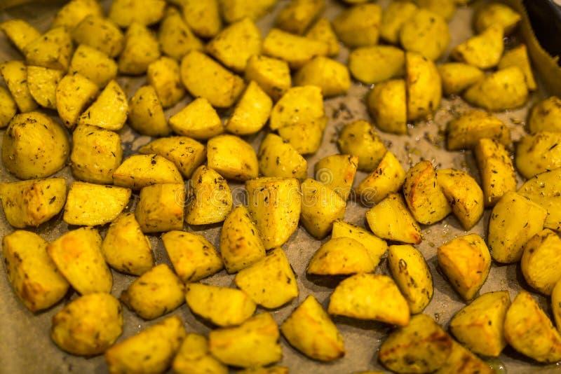Traditionella bakade guld- potatisar med Provencal kryddor arkivbild
