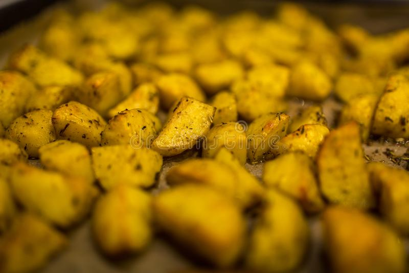 Traditionella bakade guld- potatisar med Provencal kryddor fotografering för bildbyråer